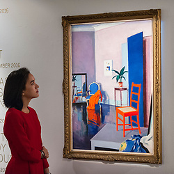 "© Licensed to London News Pictures. 18/11/2016. London, UK. A staff member views ""Interior, The Red Chair"" by Francis Campbell Boileau Cadell (est. GBP250-350k), at the preview at Sotheby's of works on view at four upcoming November auctions featuring Modern & Post-War British Art, A Painter's Paradise (Julian Trevelyan & Mary Fedden at Durham Wharf), Scottish Art and Picasso Ceramics from the Lord & Lady Attenborough Private Collection. Photo credit : Stephen Chung/LNP"