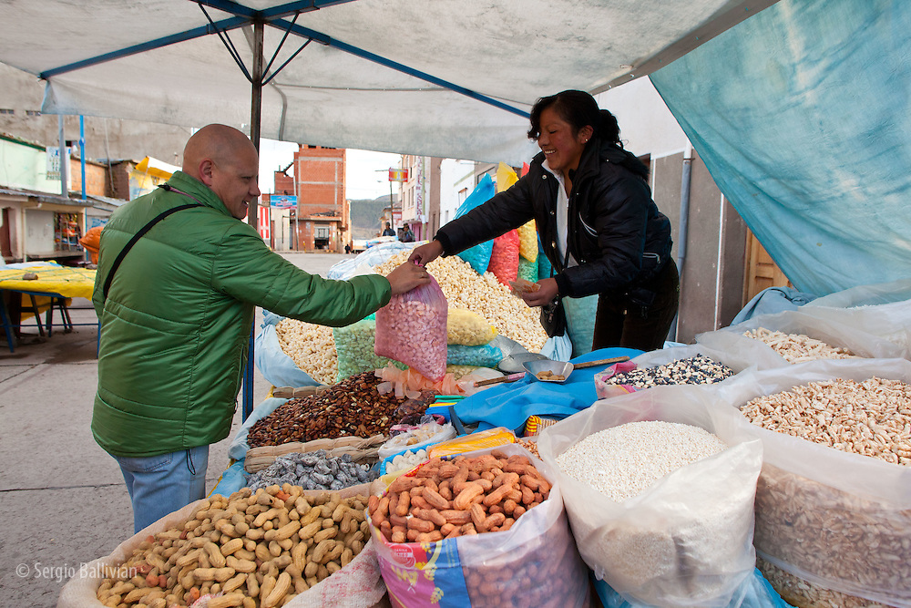 Oscar Ebert buys pasancalla (popped corn) from an open-air vendor in Copacabana, Bolivia in the early morning.