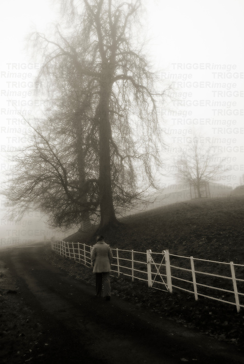 woman on country lane walking beside a white fence