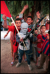 Palestinian children show their support for the Intifada, as they wait outside Shifa Hospital in Gaza City to witness the daily parade of the dead and wounded brought in by ambulance. (Photo © Jock Fistick)