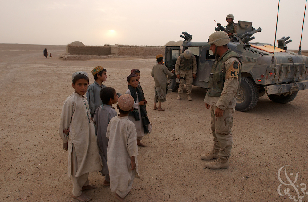 Members of the U.S. Army  3rd Platoon 108 MP company talk with local Afghan children as they patrol May 12, 2002 near the Kandahar airfield in southern Afghanistan. U.S. soldiers routinely patrol the area as part of the ongoing coalition Operation Enduring Freedom.