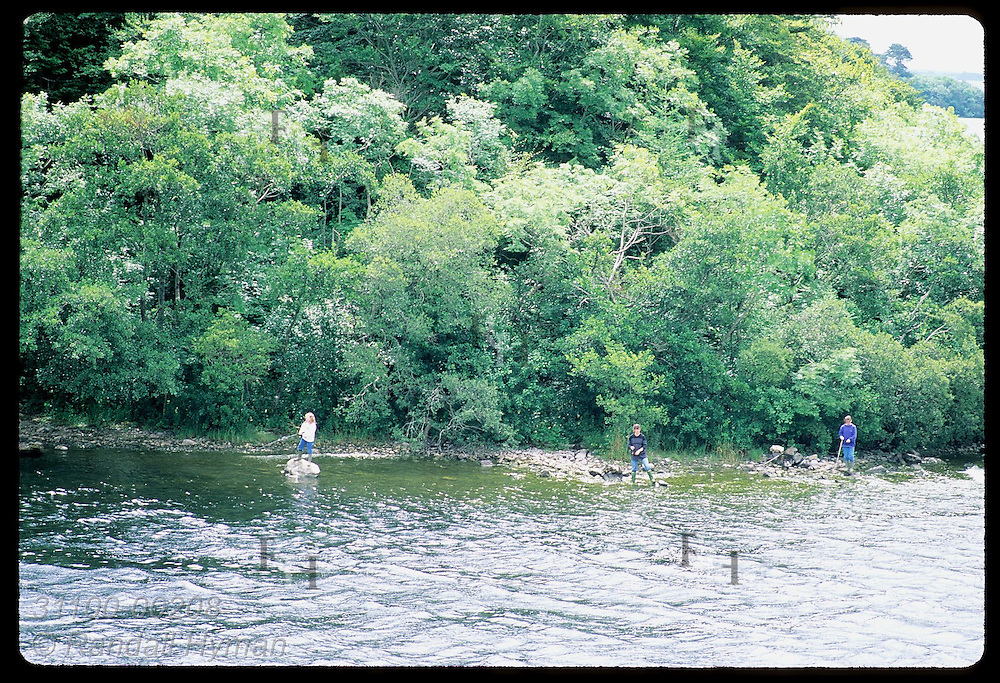 Three people fish along the wooded shores of Lough Corrib near the village of Cong. Ireland