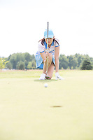Young woman aiming ball while kneeling at golf course