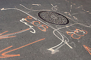 A manhole cover is surrounded by spray painted symbols and letters on an Upper East Side street in Manhattan.
