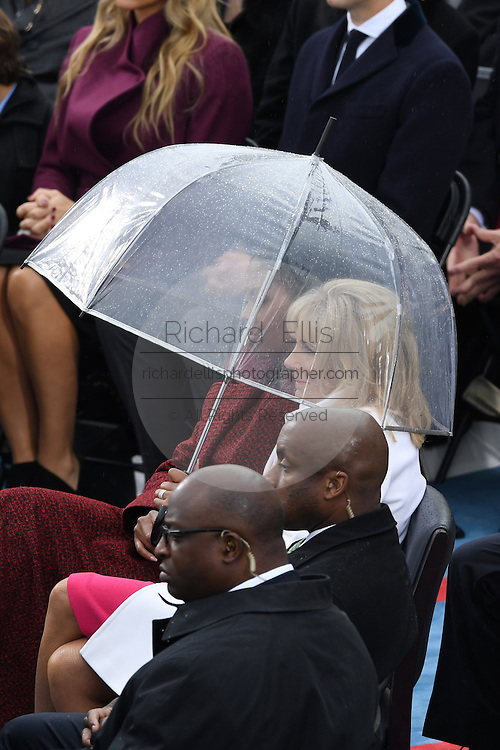 First Lady Michelle Obama and Dr. Jill Biden sit under an umbrella during a brief rain at the 68th President Inaugural Ceremony on Capitol Hill January 20, 2017 in Washington, DC. Donald Trump became the 45th President of the United States in the ceremony.