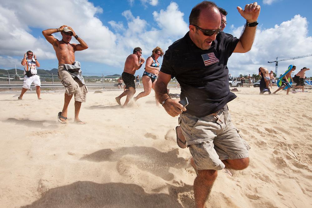 Dutch Antilles, Sint Maarten, Tourists running from sand blasted by departing passenger jet on Sunset Beach at Princess Juliana International Airport