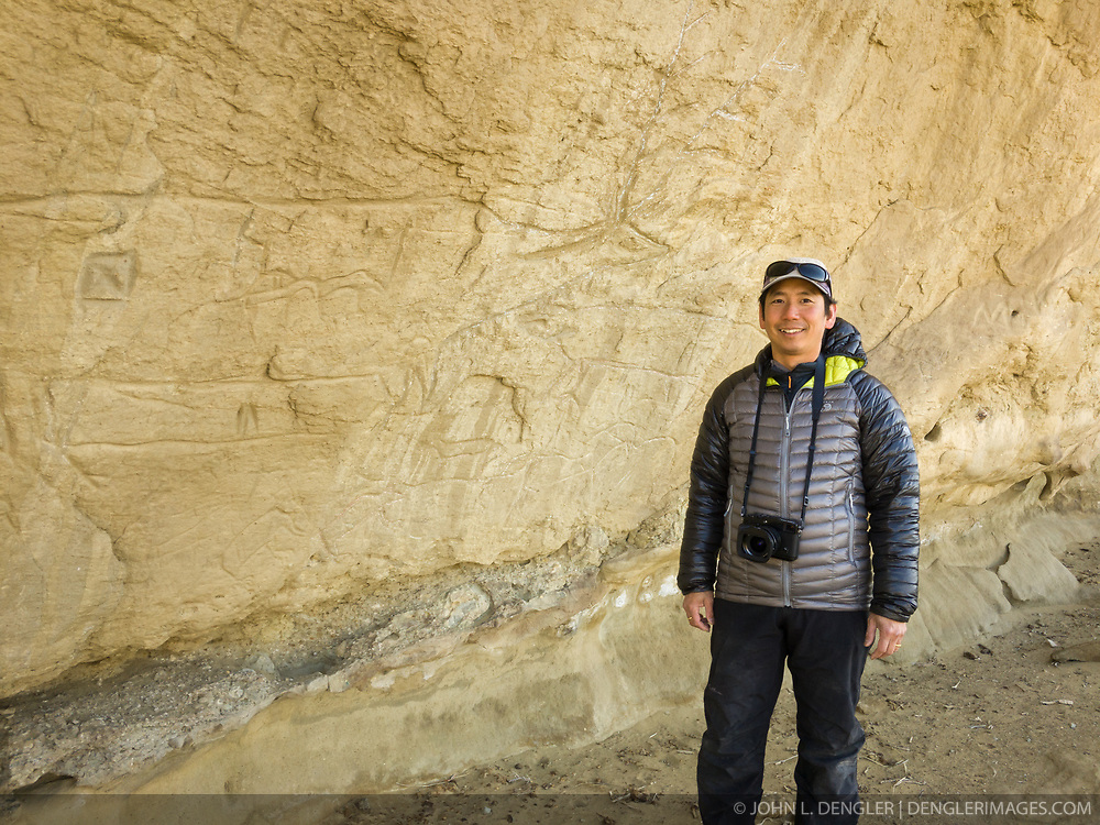Wildlife photojournalist Noppadol Paothong poses for a photo next to native American petroglyphs at the White Mountian petroglyphs site in Wyoming. ©John L. Dengler / DenglerImages.com