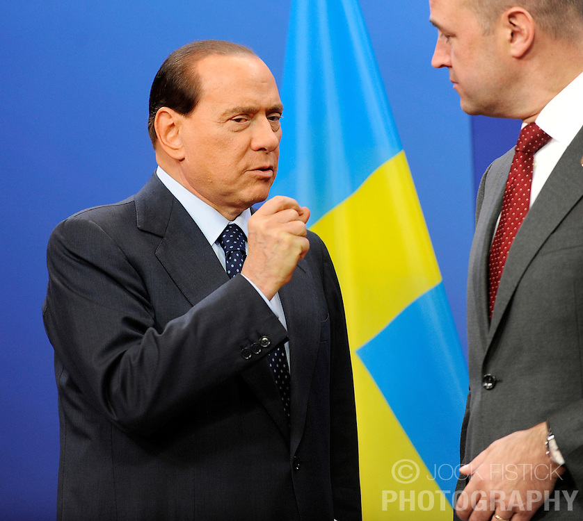 Silvio Berlusconi, Italy's prime minister, left, speaks with Fredrik Reinfeldt, Sweden's prime minister and standing president of the European Council, as he arrives for the European Summit at the EU headquarters in Brussels, Belgium, on Thursday, Sept. 17, 2009. European Union leaders may call for sanctions on banks that pay excessive bonuses, fearing that runaway executive pay could trigger another financial crisis, a draft text showed. (Photo © Jock Fistick) *** Local Caption ***Silvio Berlusconi