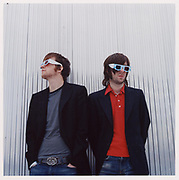 Two men leaning against wall wearing 3D glasses.