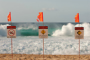 The high surf on the North Shore of Oahu brings warning signs on the beaches to warn swimmers of the danger.