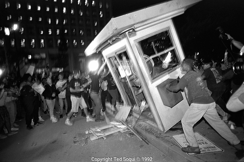 Rioters overturn and burn a parking kiosk near Parker Center, LAPD headquarters, in downtown Los Angeles.<br /> <br /> Los Angeles has undergone several days of rioting due to the acquittal of the LAPD officers who beat Rodney King.<br /> Hundreds of businesses were burned to the ground and over 55 people have been killed.