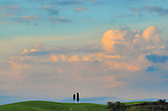Ominous stormy clouds approaching the enchanted rural sceneries of the Orcia Valley in Tuscany, Italy. Taken at sunset in the hills between San Quirico d'Orcia and Bagno Vignoni.