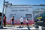 Visitors wait near the historic Bayside Canning Company building for a free shuttle for parking during Santa Clara County Parks Day on the Bay event at Alviso Marina County Park in Alviso, California, on October 13, 2013. (Stan Olszewski/SOSKIphoto)