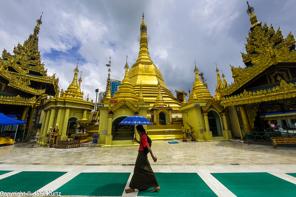 12 JUNE 2013 - YANGON, MYANMAR: People walk through Sule Pagoda in Yangon, Myanmar. Sule Pagoda is one of the city's oldest and most revered Buddhist temples and landmark for central Yangon.        PHOTO BY JACK KURTZ