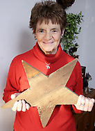 "Marolyn Ray holds a wooden star from her grandparents farm near Spencerville, Ohio.  The star, which is around 100 years old, was high on the south side of the barn, and she says, ""I was sure that if I could manage to climb up to the star I could see all the states."""