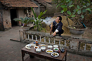 Nguy?n V?n Theo, a rice farmer, in his courtyard in Tho Quang village, outside Hanoi, Vietnam, with his typical day's worth of food. (From the book What I Eat: Around the World in 80 Diets.) The caloric value of his day's worth of food on a typical day in December was 2500 kcals. He is 51 years of age; 5 feet, 4 inches tall; and 110 pounds. Behind him is a pile of last year's rice straw, used for fuel to boil water in the family's small kitchen. Rainwater from the tile roof of the main house fills a cement cistern, providing water for drinking and cooking. Theo enjoys the relative tranquility of village life, compared to his wife's busy routine of selling fresh produce on the sidewalks of Hanoi. Floods ruined his rice crop a few months ago, so after last year's store of rice is eaten, the family will rely on his wife's income to buy this staple grain until he harvests the next crop. MODEL RELEASED.
