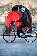 A man cycling past a red door