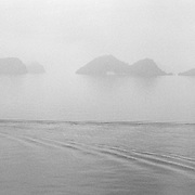 A local fishing boat navigates the waters in the early morning mist in Ha Long Bay, Vietnam. The bay consists of a dense cluster of 1,969 limestone monolithic islands. Ha Long Bay, is a UNESCO World Heritage Site, and a popular tourist destination. Ha Long, Bay, Vietnam.  Photo Tim Clayton