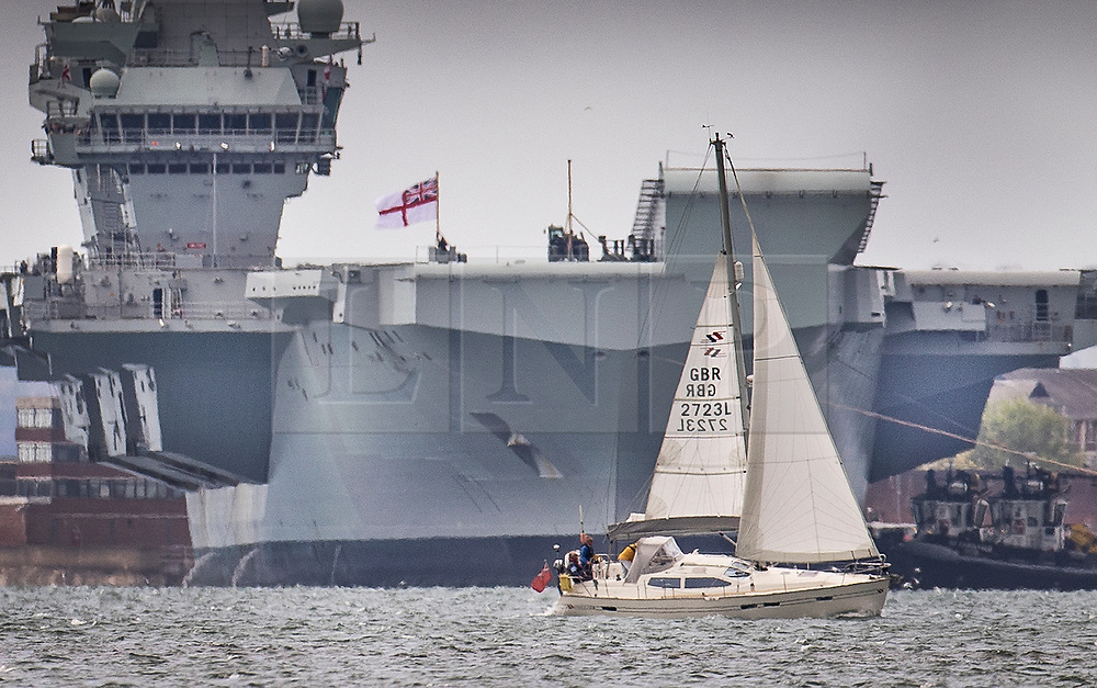 © Licensed to London News Pictures. 02/07/2020. Portsmouth, UK. A yacht sails near Royal Navy aircraft carrier HMS Queen Elizabeth as she sails into Portsmouth harbour. The 65,000 tonne supercarrier has been at sea for 10 weeks conducting trials of the new F35 Lightening fighter jets ahead of her first operational mission in 2021. Photo credit: Peter Macdiarmid/LNP