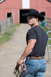 cowboy turning around as he walks towards a barn