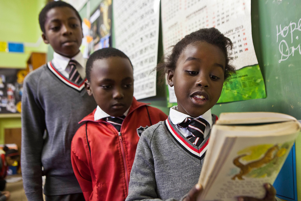 A young school girl happily reads out loud to her class in a classroom in St Agnes Primary School, Woodstock, Cape Town, South Africa.  Two boys stand behind her also looking at the book and waiting for their turn to read.  They are standing in a queue by the green board at the front of the class and wear school uniform.