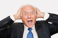 Portrait of shocked elderly businessman against white background