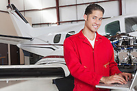 Portrait of young aeronautic engineer using laptop in front of airplane