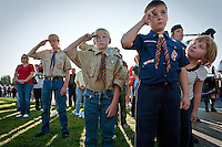 JEROME A. POLLOS/Press..Kaylee Thomas, 6, checks to see if her brother, Craig Thomas, 9, is saluting alongside his fellow scouts Josh Kirby, 10, and Zak Kirby, 14, during the retirement of the colors at the dedication ceremony Friday for the Fallen Heroes Memorial Plaza in Coeur d'Alene.