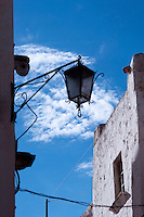 Un particolare di un lampione nel borgo antico di Ostuni, in contrasto con il bianco della casa sullo sfondo ed un cielo azzurro.