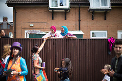 © Licensed to London News Pictures . 13/08/2016 . Manchester , UK . Residents watch the annual Caribbean Carnival Parade as it passes through Hulme and Moss Side in South Manchester . Photo credit : Joel Goodman/LNP