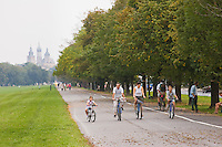 Family cycling in Blonia Park with St Mary's Basilica behind in Krakow Poland