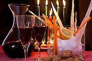 red wine still life composition with wine, snow, small ice stalactites, vegetables,walnuts and candles.