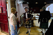 A piper greeting guests arriving for a St. Andrew's dinner dance held by the Sandbach and District Caledonian Society at Sandbach Town Hall, Cheshire, England on St. Andrew's Day. Around 40 people from the Society attended the meal and dance which included a programme of Scottish country dancing. St. Andrew was the patron saint of Scotland and the day was celebrated by Scots worldwide on the 30th November.