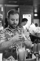 Stephen Caronna of Lei Low swizzles a tiki cocktail. (Editorial)