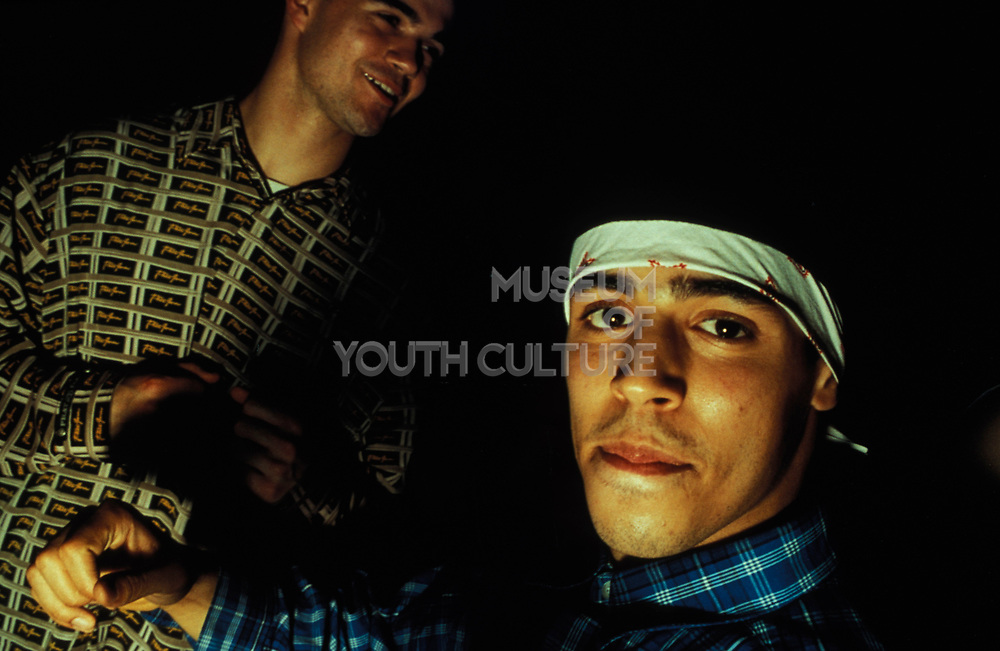 Two men in chequered shirts, one wearing folded bandana on forehead, Le Batoter, Paris, France, 2000.