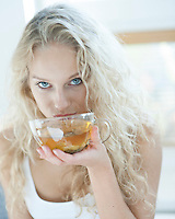 Portrait of sensuous woman drinking herbal tea in house