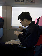 businessman eating a traditional bento lunch while traveling by train