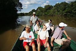 "A group of French tourists take a river boat cruise in Los Llanos in Venezuela. Los LLanos are the grasslands in western Venezuela famous for the ""llanera"" culture of cowboys and music.  Many working ""Hatos"" , or cattle ranches, dot the landscape of grasslands and river systems, offering tourists a chance to see the beautiful landscape and various wildlife.  Tourists go out on land and water excursions where they get a chance to see see caiman, orinoco crocodile, anaconda, piranha, numerous bird species and capybara, the world's largest rodent."
