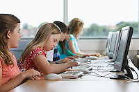 Children (10-12) using computer in computer lab