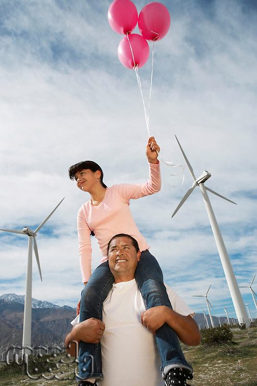 Girl (7-9) holding balloons, sitting on fathers shoulders at wind farm