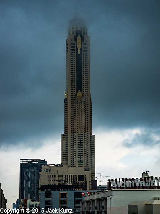 """16 SEPTEMBER 2015 - BANGKOK, THAILAND: The top of Baiyoke Tower II is obscured by clouds during a rain storm in Bangkok. It's 304 meters (997 feet) tall and the tallest skyscraper in Bangkok. It has a hotel with more than 600 rooms and a rooftop observation deck.  The remnants of tropical storm """"Vamco"""" hit Bangkok Wednesday. Storm, downgraded to a tropical depression, brought bands of rain to central Thailand, including Bangkok. The Thai Meteorological Department said the storm would help alleviate the drought that has gripped Thailand since late last year.     PHOTO BY JACK KURTZ"""