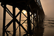 Thick fog blankets Isle of Palms beach pier at sunrise near Charleston, South Carolina.