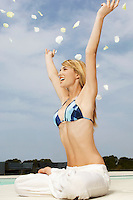 Young woman sitting by swimming pool throwing flower petals in air full length