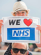 NHS supporters in the crowd with placards. The NHS choir performs on the Pyramid stage - The 2016 Glastonbury Festival, Worthy Farm, Glastonbury.