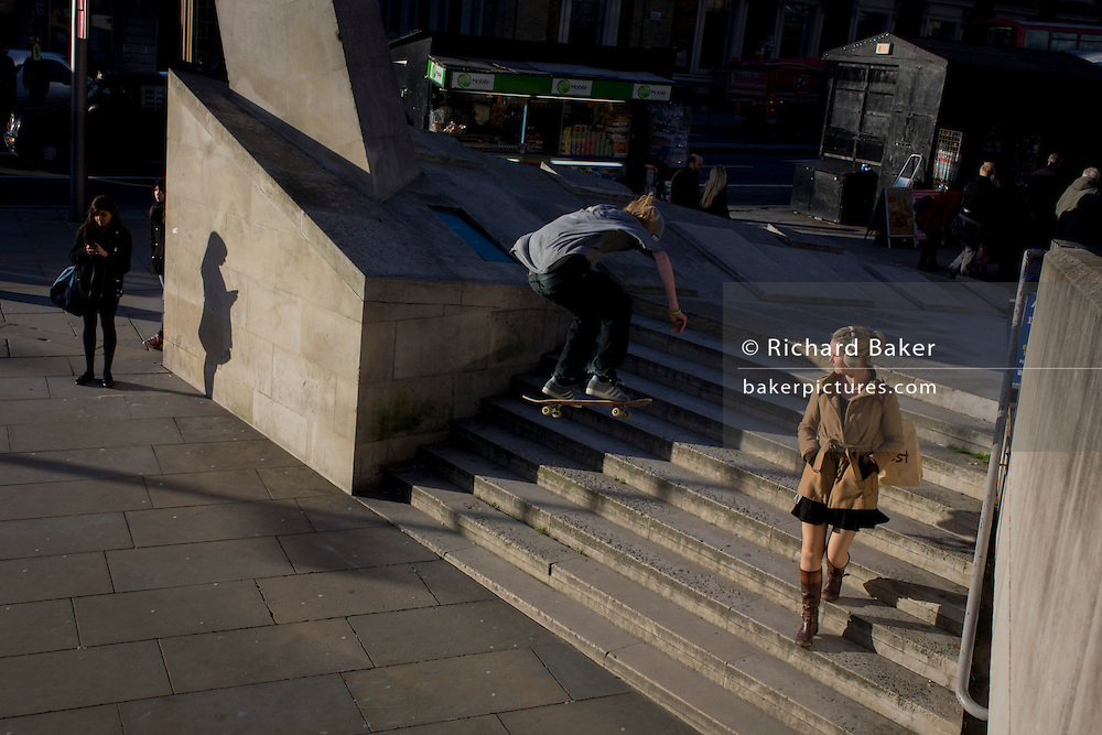 Young women are unaware of a young skateboarder suddenly flying through the air during his acrobatic jump over steps during London's rush hour.