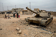 A family walks past a destroyed American M-1 Abrams tank in Gogjali, Iraq. Nov. 30, 2016. (Photo by Gabriel Romero ©2016)