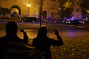 George Washington University students all 18, look down 15th Street NW in Washington, D.C. to catch a glimpse of President Barack Obama's motorcade as he returned to Washington from Chicago on Wednesday evening. Each of the students voted for the first time in this year's eleciton.