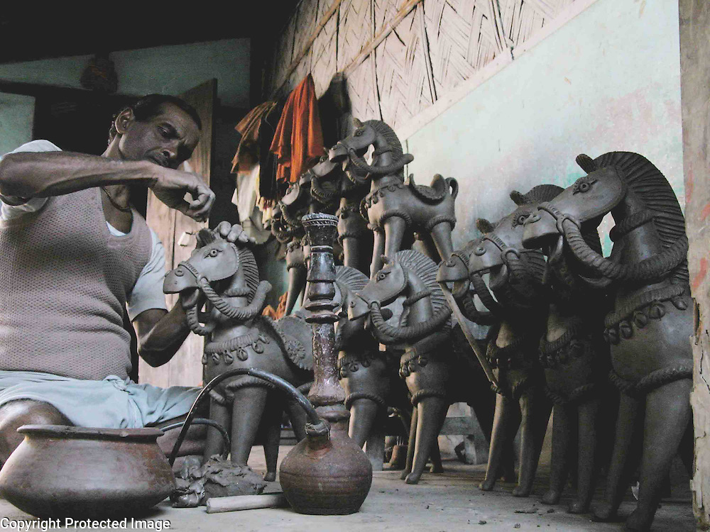 "Madhav Pal, national award winner of  handicraft is busy to make the world famous ""Terracotta"" doll at Asharikandi, about 291 kilometres southwest of Guwahati, capital of North-Eastern Indian State of Assam..Including national and international award winner, more than 80% families are engaged in this ethnic-art (handicraft) and pass their life after sell these Terracotta product in the national and international market, while the Government has declared this village as a model village. (Photo/Shib Shankar Chatterjee)."