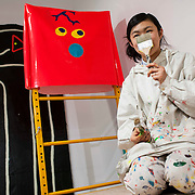 "March 10, 2012 - New York, NY : Sitting atop a painter's scaffolding, artist Misaki Kawai hides from the camera behind a painters' brush as she continues the painting and installation of her new exhibit ""Love from Mt. Pom Pom,"" at the Children's Museum of the Arts in the south village on Saturday March 10. CREDIT: Karsten Moran for The New York Times"