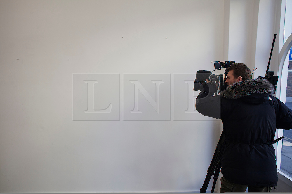 """© Licensed to London News Pictures. 11/12/2013. London, United Kingdom. A television cameraman films an empty wall where the paintings hung. The gallery """"Exhibitionist"""" in 15b Blenheim Crescent London. Two of artist Damien Hirst's paintings were stolen from the gallery. Photo credit : Andrea Baldo/LNP"""
